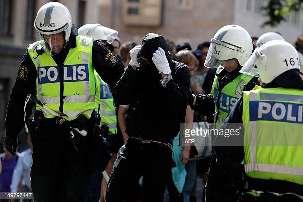 Police detain a leftist activist during an antiIslam demonstration in Stockholm on August 4 2012 Violence erupted during the demonstration a...