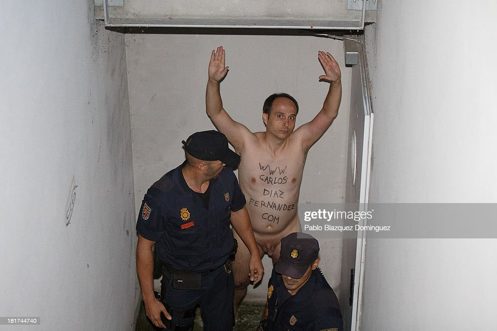 Police detain a man who demonstrated naked as Queen Sofia of Spain arrived at Quiron University Hospital, where Spain's King Juan Carlos is undergoing an operation, on September 24, 2013 in Pozuelo de Alarcon, Spain. The King is to have his left prosthetic hip replaced due to an infection.