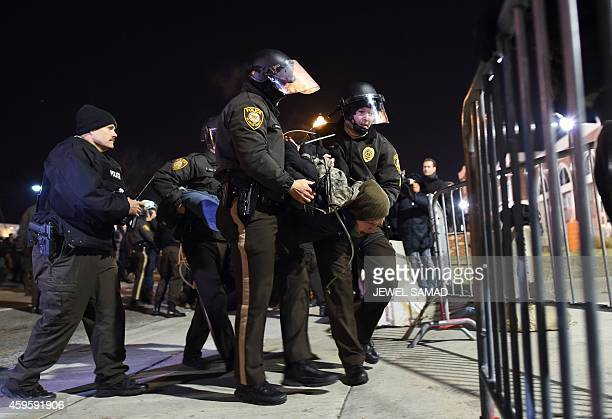 Police detain a protester outside the police station in Ferguson Missouri on November 25 2014 during a demonstration one day after violent protests...