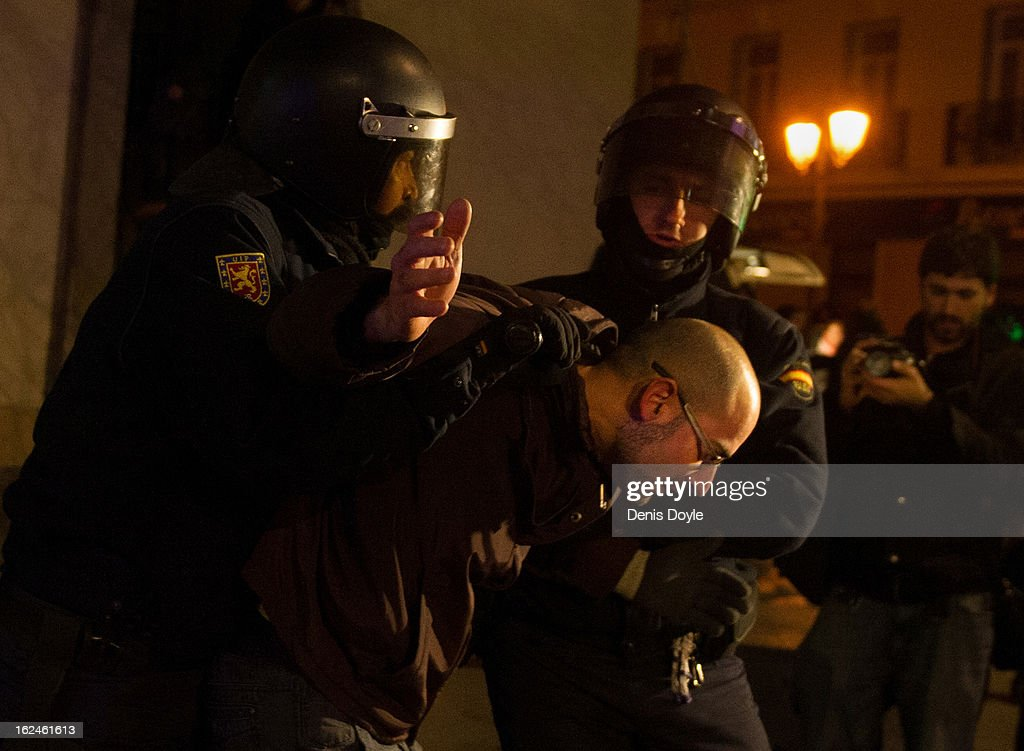 Police detain a protestor during disturbances after a march by thousands of people on February 23, 2013 in Madrid, Spain. Public health workers, civil servants and disaffected citizens converged on central Madrid to protest against the austerity measures of Prime Minister Mariano Rajoy.