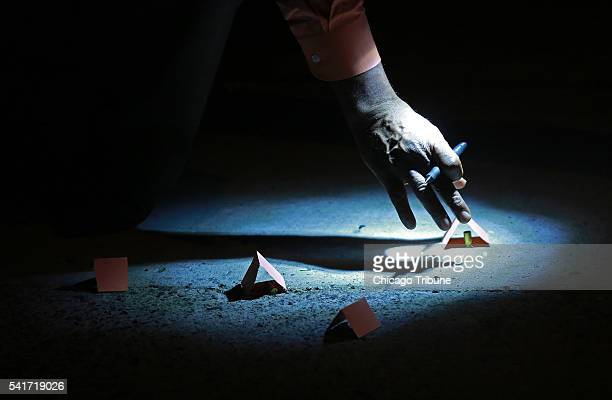 A police detective inspects bullet casings at the scene of a double shooting on the 8700 block of South Sangamon Street Saturday June 18 in Chicago...