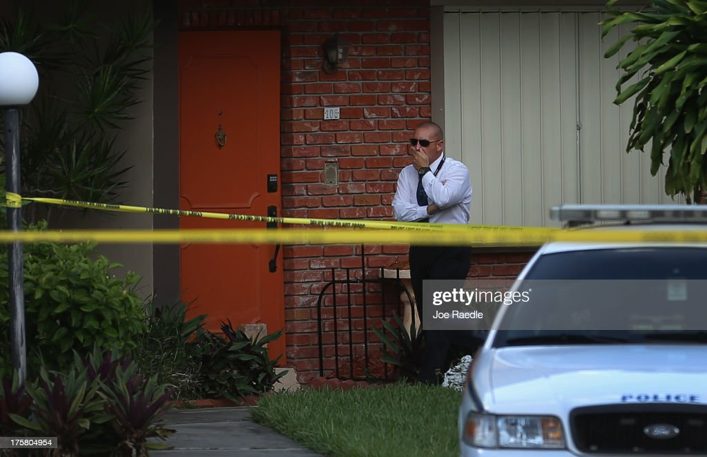 A police detective stands near the orange door which is the front door to a townhouse where seemingly a husband reportedly confessed on Facebook to murdering his wife on August 8, 2013 in Miami, Florida. After apparently murdering his wife and then posting a photo of her body, a South Miami man turned himself in to police. Miami Dade police spokesperson, Javier Baez, said that the police continue to investigate the scene and have been in contact with Facebook about the post. Reports indicate that the suspect is Derek Medina, 31.