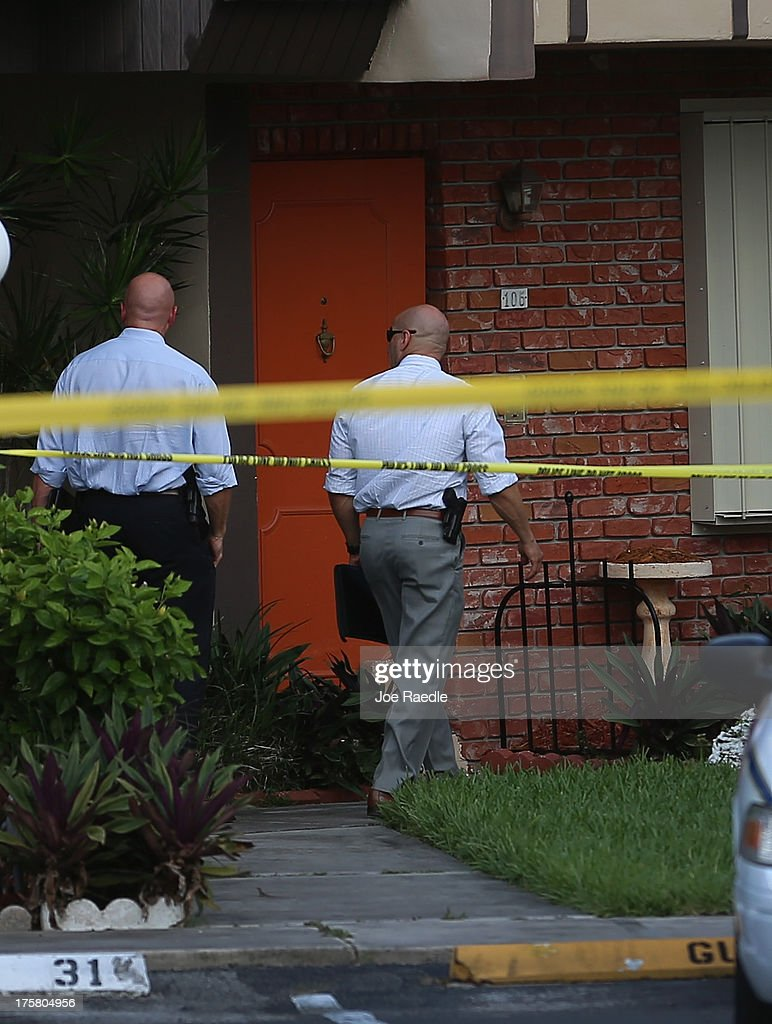 Police detectives walk past the orange door which is the front door to a townhouse where seemingly a husband reportedly confessed on Facebook to murdering his wife on August 8, 2013 in Miami, Florida. After apparently murdering his wife and then posting a photo of her body, a South Miami man turned himself in to police. Miami Dade police spokesperson, Javier Baez, said that the police continue to investigate the scene and have been in contact with Facebook about the post. Reports indicate that the suspect is Derek Medina, 31.