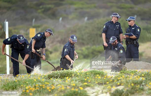 Police dig in the sand dunes after children playing at a Sydney beach on November 30 stumbled across the body of a baby buried under the sand...