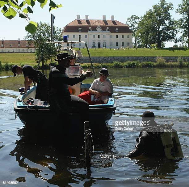 Police divers enter the lake behind Schloss Meseberg Palace the guest house of the German government during a security check a day ahead of the...