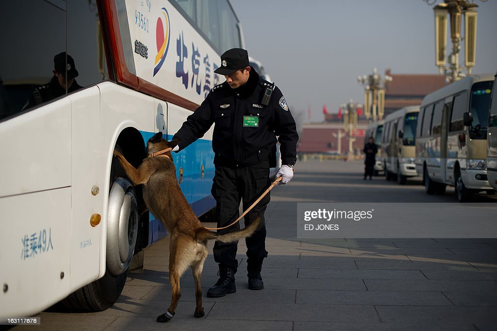 A police dog checks the buses of delegates parked on Tiananmen Square during the opening session of the National People's Congress (NPC) at the Great Hall of the People in Beijing early on March 5, 2013. China targeted 2013 economic growth of 7.5 percent and vowed an unwavering fight against corruption on March 5 at the start of an annual parliamentary session that will seal its transition to new leadership. AFP PHOTO / Ed Jones