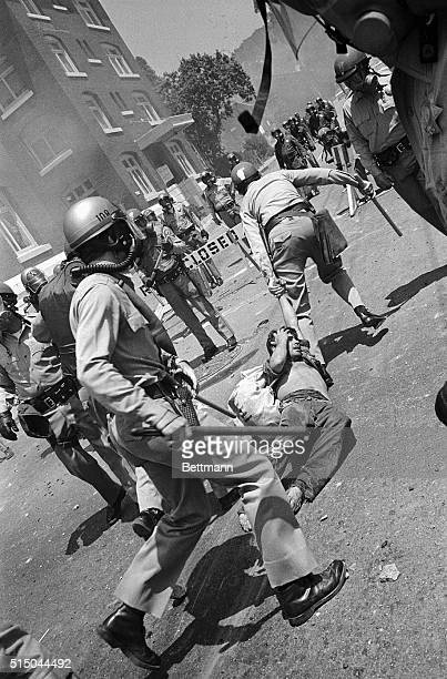 Police drag away a demonstrator injured during a clash of law enforcement officers and 2000 students and nonstudents May 15 who had recently turned a...