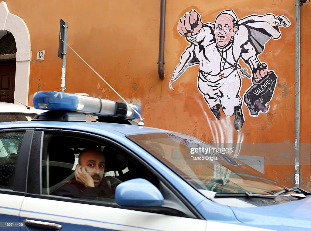 Police drives past a graffiti featuring a 'superhero' version of Pope Francis appears in Borgo Pio, next to St. Peter's Square on January 29, 2014 in Rome, Italy. The image started circulating from the twitter account of the Vatican and has rapidly spread around the world.
