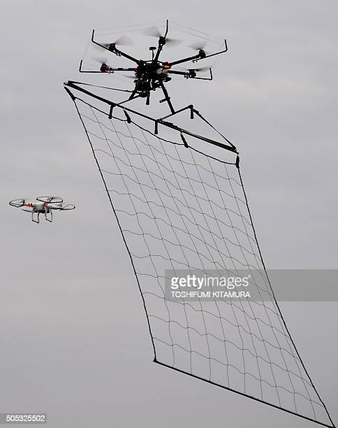 A police drone interceptor prepares to snag another drone with a net during an antiterrorism drill for the upcoming Tokyo marathon at the planned...