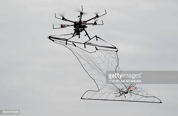 A police drone interceptor snags another drone with a net during an antiterrorism drill for the upcoming Tokyo marathon at the planned finish area...