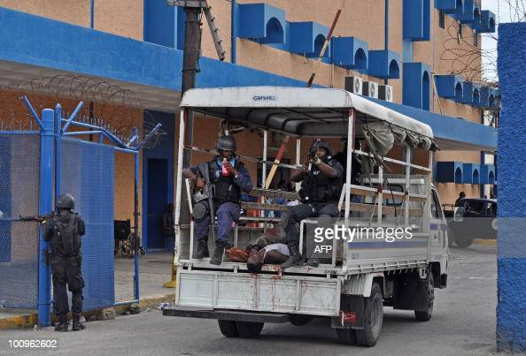 Police enter the grounds of the Kingston Public Hospital in Kingston Jamaica on May 25 2010 in a truck loaded with the bodies of 12 men The men...