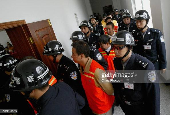 Police escort 19 gang members during a trial at the Meishan Intermediate People's Court on October 12 2005 in Meishan of Sichuan Province southwest...
