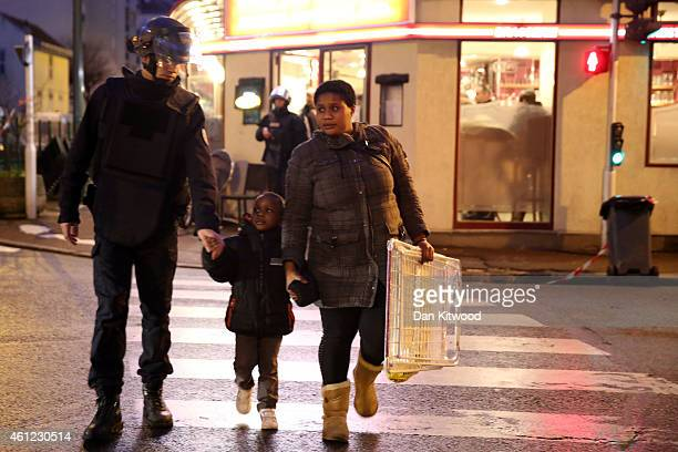 Police escort a child and woman as they mobilize at the hostage situation at Port de Vincennes on January 9 2015 in Paris France According to reports...