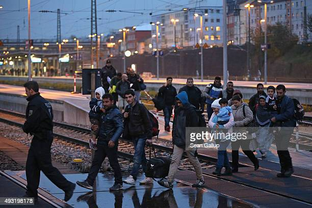 Police escort a group of migrants from countires including Iraq and Syria who had arrived on a regional train from Linz Austria to a police reception...