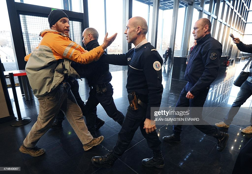 Police escort a man out of the Court of Nantes, western France, on February 24, 2014 during the trial of five protesters judged two days after a demonstration against plans to build the Notre-Dames-des-Landes airport for the French city of Nantes. Protesters smashed shop windows on February 22 and hurled paving stones at police, who answered with tear gas and rubber bullets. Tens of thousands of protesters against building the airport on protected swampland swarmed the western city's Petite Hollande square, the latest in a string of demonstrations against the pet project of Prime Minister Jean-Marc Ayrault.