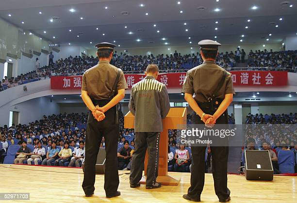 Police escort an eighteenyearold inmate as he gives a speech about his experience and shrift at a vocational school on May 24 2005 in Wuhan of Hubei...