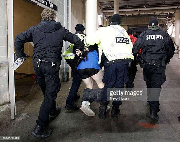Police escort an unruly fan from the stadium during the third quarter of Grey Cup 103 between the Edmonton Eskimos and Ottawa Redblacks at Investors...