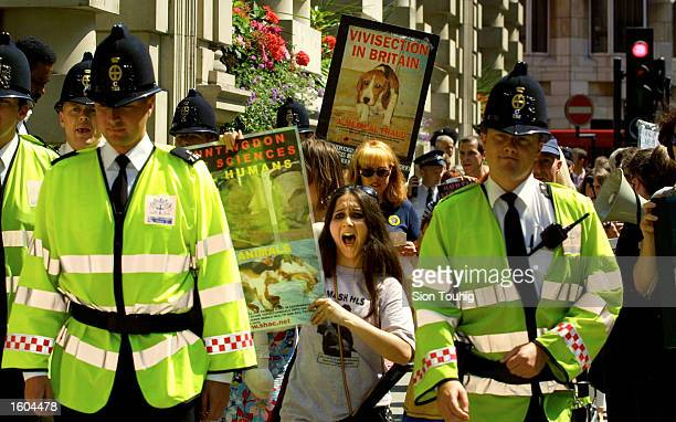 Police escort animal rights activists as they protest against experimentation on animals at Huntingdon Life Sciences July 26 2001 at the financial...