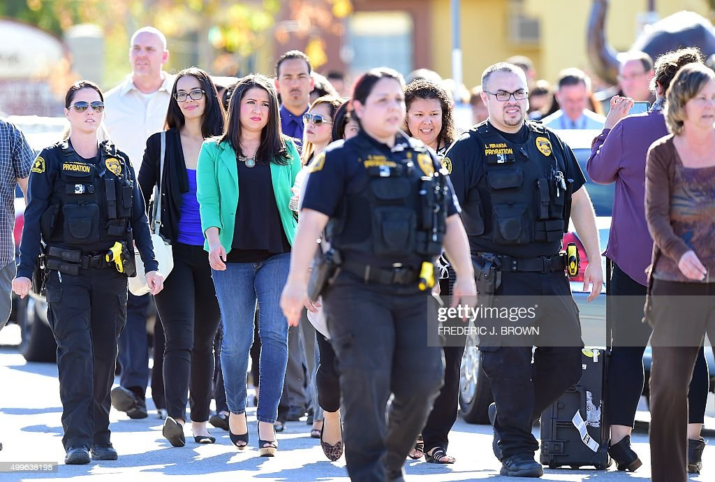 Police escort civilians away from the 1300 block of S Waterman Street near the site of a shooting took place on December 2 2015 in San Bernardino...