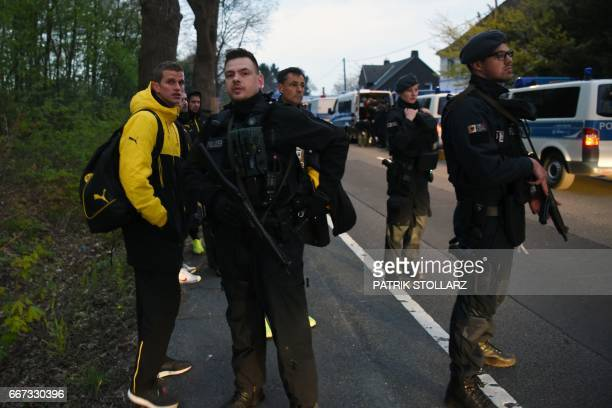 Police escort Dortmund's players including Dortmund's defender Sven Bender after the team bus of Borussia Dortmund had some windows broken by an...