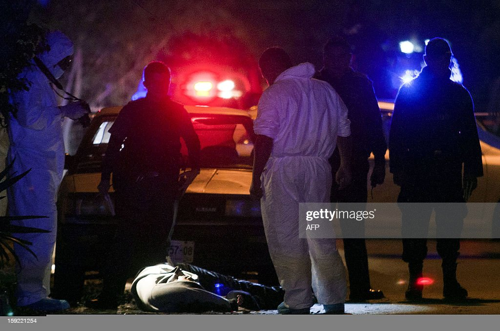 Police escort forensic service personnel as they check one (centre L) of four corpses at a crime scene in Moderna town in the City of Monterrey, Nuevo Leon state on January 10, 2013. The three men and one woman were executed inside a house by gunmen according to the police.
