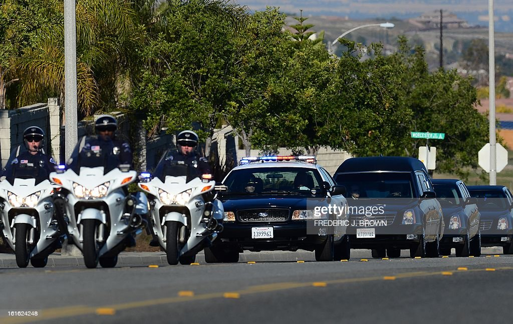 Police escort leads a convoy of vehicles, including the hearse (3rdR) carrying the body of slain Riverside police officer Michael Crain on its approach to the Grove Community Church in Riverside, California, on February 13, 2013. Law enforcement personnel from across the state, and others close to the deceased gathered to pay their final respects to the policeman killed last week in what the city's police chief described as a 'cowardly ambush.'' Crain was fatally shot last Thursday when he and his partner ran afoul of fugitive Christopher Jordan Dorner, the fired Los Angeles Police Department officer on a killing spree which ended last night in the mountains of nearby Big Bear, authorities report. AFP PHOTO / Frederic J. BROWN