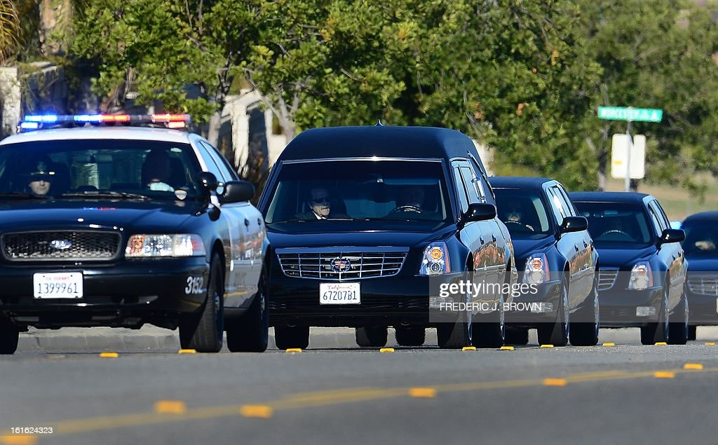Police escort leads a convoy of vehicles, including the hearse (2ndL) carrying the body of slain Riverside police officer Michael Crain on its approach to the Grove Community Church in Riverside, C...