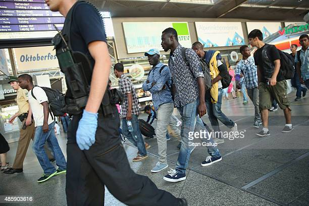 Police escort migrants who had arrived at Munich Hauptbahnhof main railway station on a train from Bologna Italy but who had no passports to a...