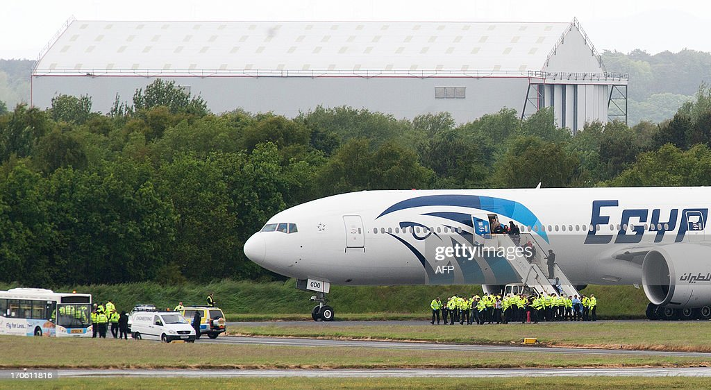 Police escort passengers off the egyptair boeing 777 flight from pictures getty images - Egyptair airport office number ...
