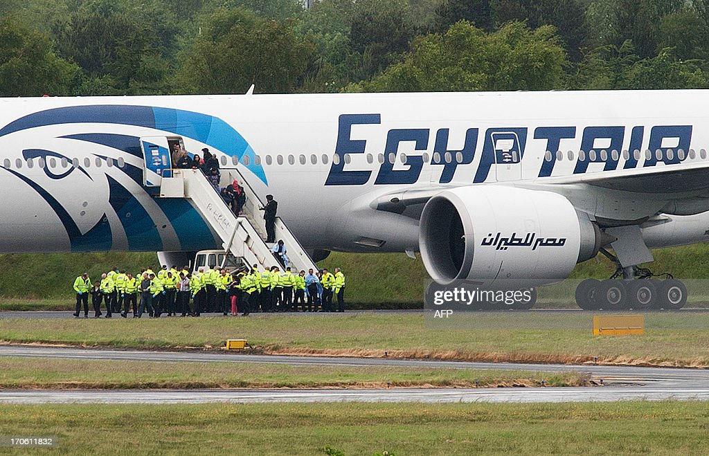 Police escort passengers off the Egyptair Boeing 777 flight from Cairo that was forced to land at Glasgow Prestwick airport in Scotland on June 15, 2013 en route to JFK airport in New York after an onboard incident. Britain's Royal Air Force (RAF) on June 15 escorted an Egyptair plane bound for New York to a Scottish airport following an onboard incident, the Ministry of Defence said. The Boeing 777 was travelling between Cairo and New York when a passenger alerted plane crew that she had found a note reading 'I'll set this plane on fire' in the toilet. The message was scrawled in pencil on a napkin and was found by BBC New York producer Nada Tawfik.