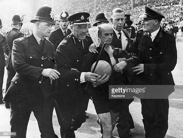 Police escort referee R Kritlin of West Germany off the pitch at the end of the World Cup match between England and Argentina during which he sent...