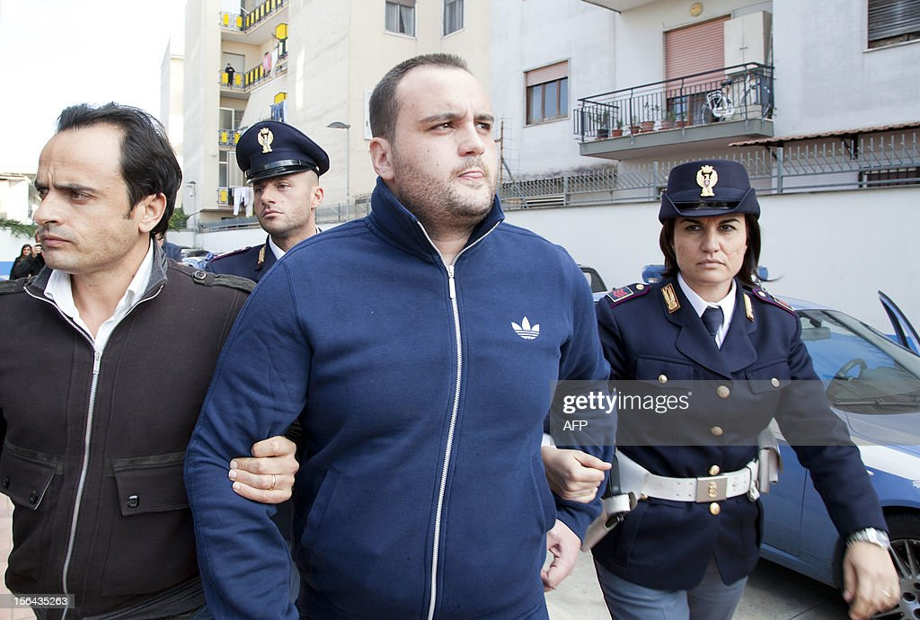 Police escort the boss of Girati mafia clan in Frattamaggiore, Rosario Guarino (C), nicknamed 'Joe Banana' during his arrest on November 15 2012 in Naples. AFP PHOTO / CARLO HERMANN