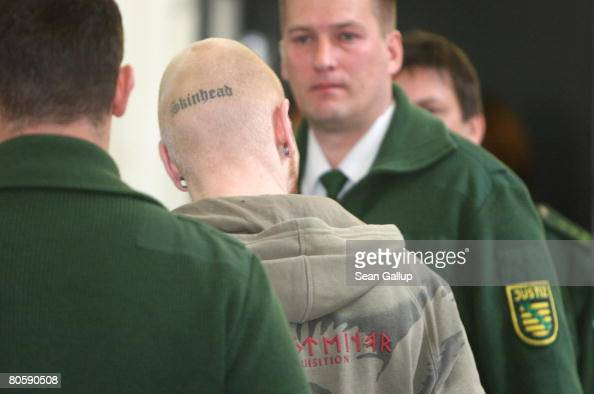 Police escort Tom W who has the word Skinhead tatooed to the back of his skull in handcuffs to court on the first day in the trial of him and four...