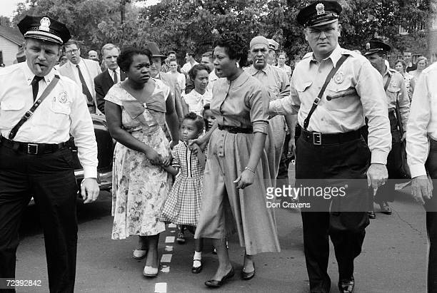 Police escorting African American mothers with grade school kids past jeering mob of demonstrators after the desegregation of the school