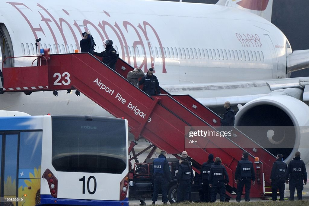 Police evacuate passengers on February 17, 2014 from the Ethiopian Airlines flight en route to Rome, which was on hijacked and forced to land in Geneva, where the hijacker has been arrested, police said. There were no immediate reports of injuries and in a statement in Addis Ababa Ethiopian Airlines said 'the passengers are safe and sound.' AFP PHOTO / Richard Juilliart