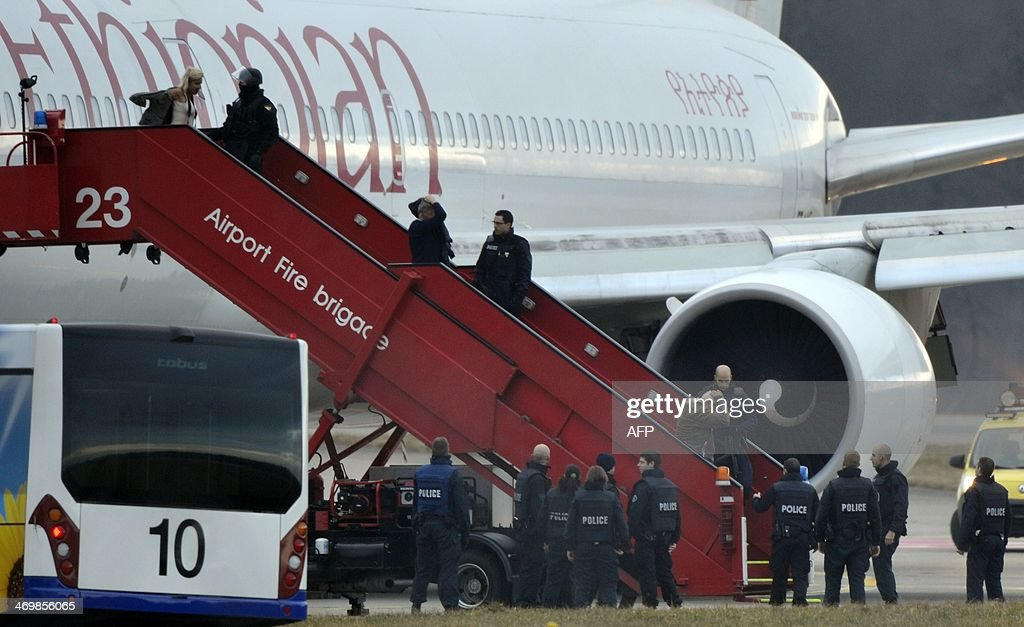 Police evacuate passengers on February 17, 2014 from the Ethiopian Airlines flight en route to Rome, which was on hijacked and forced to land in Geneva, where the hijacker has been arrested, police said. There were no immediate reports of injuries and in a statement in Addis Ababa Ethiopian Airlines said 'the passengers are safe and sound.' According to the ATS news agency, the flight was carrying some 200 people and was hijacked as it flew over Sudan, but the reason for the hijacking was not immediately clear. AFP PHOTO / Richard Juilliart