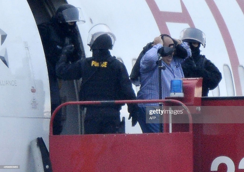 Police evacuate passengers on February 17, 2014 from the Ethiopian Airlines flight en route to Rome, which was hijacked and forced to land in Geneva, where the hijacker has been arrested, police said. There were no immediate reports of injuries and in a statement in Addis Ababa Ethiopian Airlines said 'the passengers are safe and sound.' The hijacker was the co-pilot, according to the Geneva airport where the plane was forced to land. AFP PHOTO / Richard Juilliart