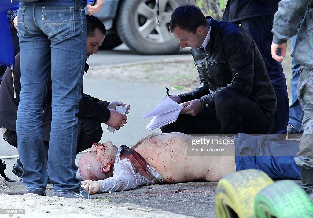 Police experts examine the body of prominent pro-Russian journalist Oles Buzyna aged 45, after he was shot dead in Kiev on April 16, 2015. Buzyna known for his pro-Russian views was gunned down in broad daylight in Kiev.