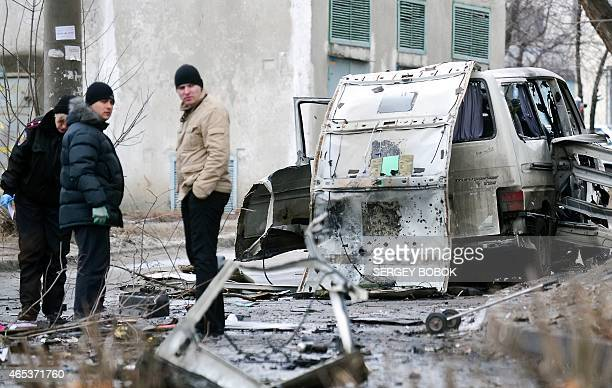 Police experts examine the wreckage of a minibus following a blast in Kharkiv on March 6 2015 The head of a volunteer battalion and his wife who is...