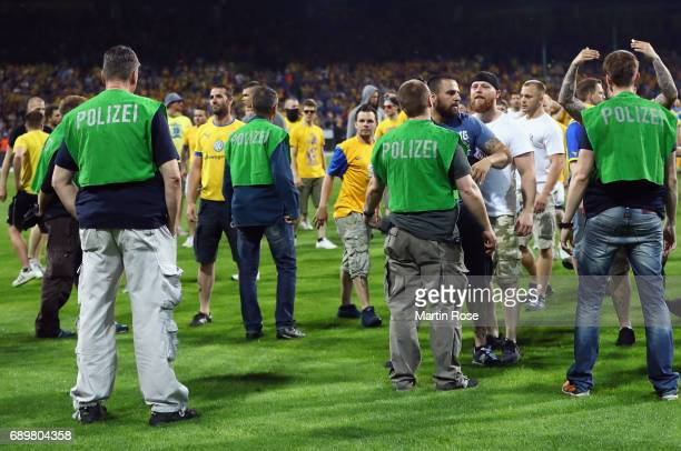 Police face Braunschweig fans after the Bundesliga Playoff leg 2 match between Eintracht Braunschweig and VfL Wolfsburg at Eintracht Stadion on May...