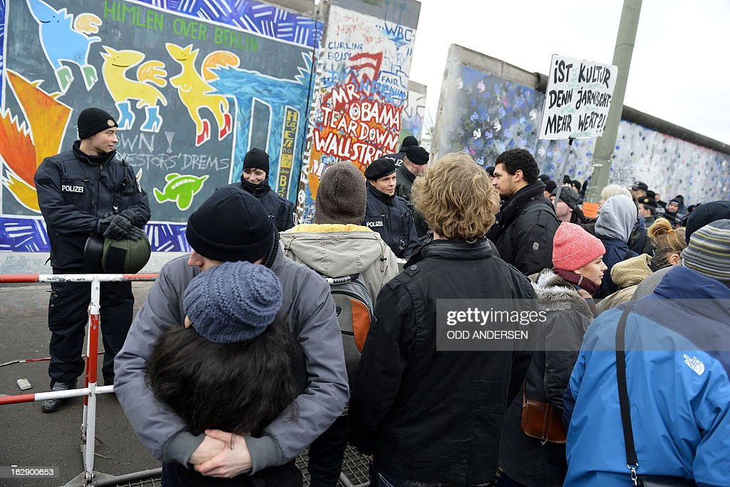 Police face protesters with a banner reading 'Does culture still means anything?' during the removal of a section of the East Side Gallery, a 1,3 km long remainder of the Berlin Wall, for a housing construction project near the city's east railway station in Berlin on February 28, 2013. Some 25 meters of this section of the wall that mostly came down 23 years ago and marked the end of the cold war are taken away to make way for a new housing development on river Spree, a project called Living Levels. As news of this spread activists and artists that had decorated this remaining part of the cold war relic known as the east side gallery came to protest.