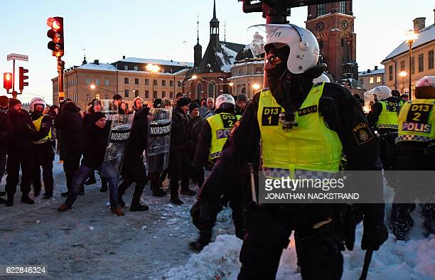 Police faces neonazi Nordic Resistance Movement sympathisers demonstrating in central Stockholm on November 12 2016 to protest against migrants / AFP...