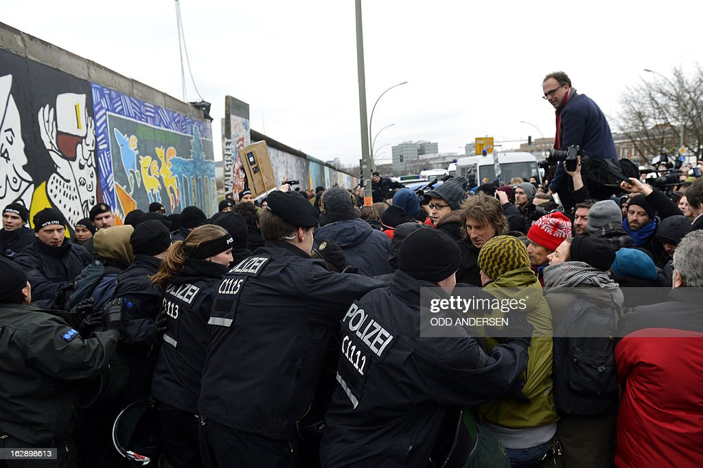Police faces people protesting against the removal of a section of the East Side Gallery, a 1,3 km long remainder of the Berlin Wall, for a housing construction project near the city's east railway station in Berlin on March 1, 2013. Some 25 meters of this section of the wall that mostly came down 23 years ago and marked the end of the cold war are taken away to make way for a new housing development on river Spree, a project called Living Levels. As news of this spread activists and artists that had decorated this remaining part of the cold war relic known as the east side gallery came to protest.