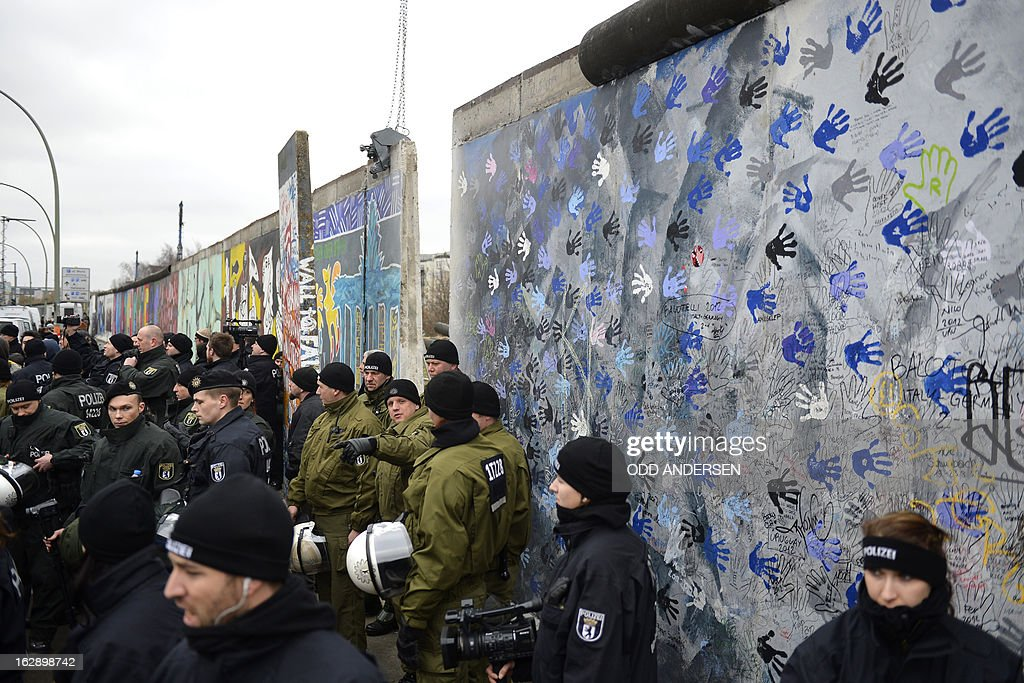 Police faces protesters during the removal of a section of the East Side Gallery, a 1,3 km long remainder of the Berlin Wall, for a housing construction project near the city's east railway station in Berlin on March 1, 2013. Some 25 meters of this section of the wall that mostly came down 23 years ago and marked the end of the cold war are taken away to make way for a new housing development on river Spree, a project called Living Levels. As news of this spread activists and artists that had decorated this remaining part of the cold war relic known as the east side gallery came to protest. AFP PHOTO / ODD ANDERSEN