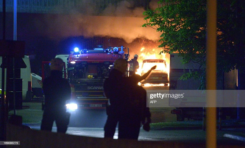 Police faces youths rioting in northern Stockholm on Sunday night and early morning Monday on May 20, 2013, setting fire to cars and throwing rocks at police, in what is believed to be a protest against the fatal police shooting of a machete-wielding man in the suburb last week.