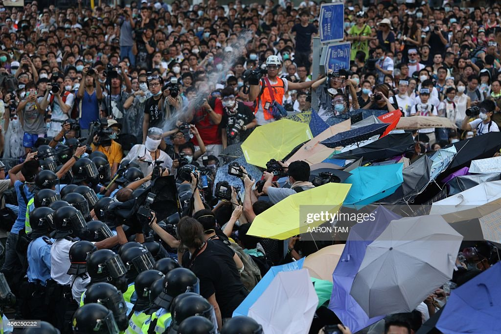 Police fire pepper spray towards prodemocracy demonstrators near the Hong Kong government headquarters on September 28 2014 Police fired tear gas as...