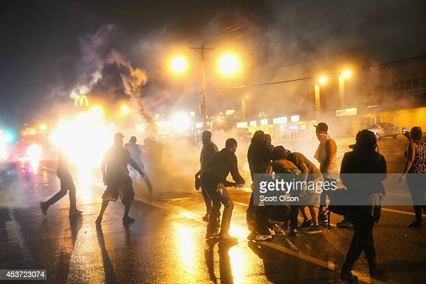 Police fire tear gas at demonstrators protesting the shooting of Michael Brown after they refused to honor the midnight curfew on August 17 2014 in...