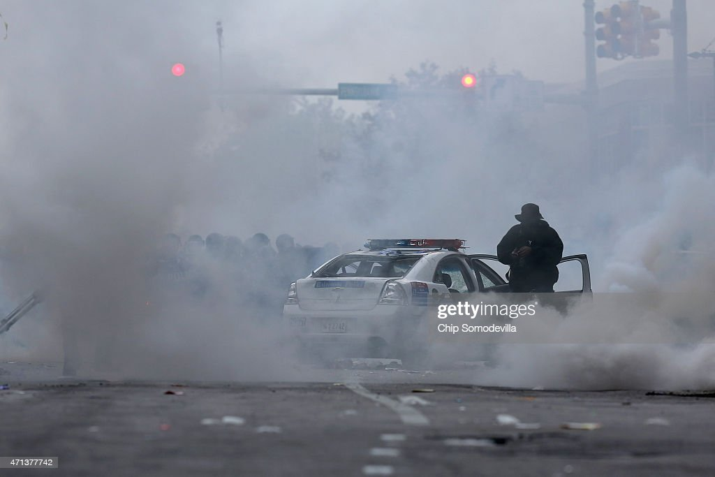 Police fire tear gas canisters as violent protests move along Pennsylvania Avenue following the funeral of Freddie Gray April 27 2015 in Baltimore...