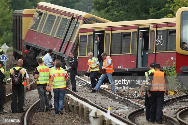 Police firemen and emergency rescue workers stand around the wreckage of a derailed SBahn commuter train on August 21 2012 in Berlin Germany The...