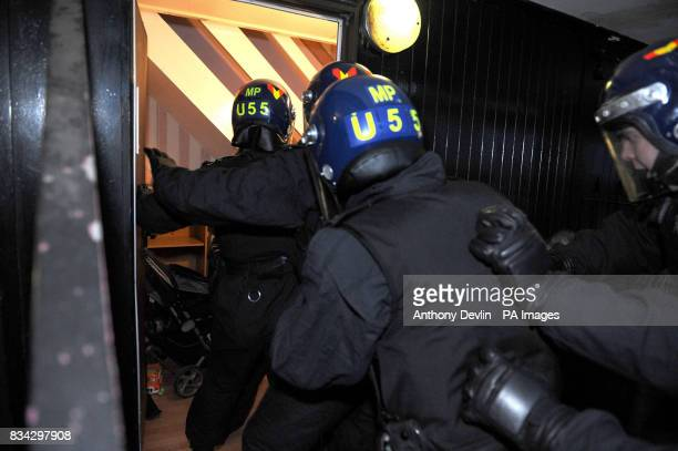 Police force make their way into a property at Six Aces in Finsbury Park at dawn as part of Operation Mista